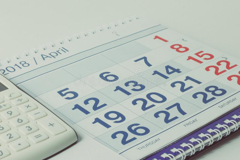 Calculator and pen on calendar background royalty free stock images