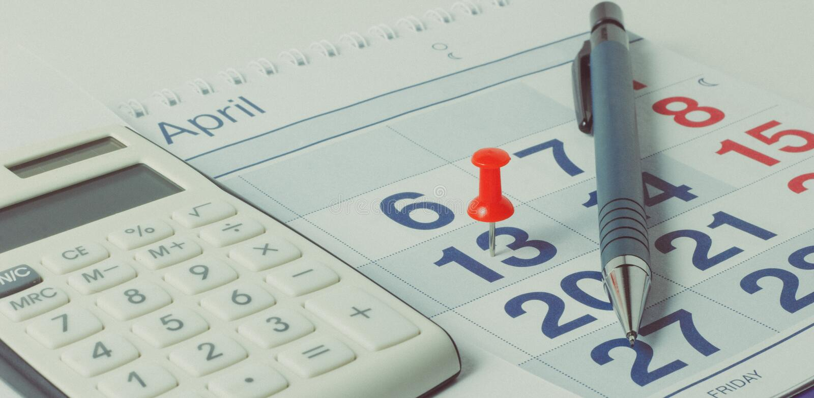 Calculator and pen on calendar background royalty free stock image