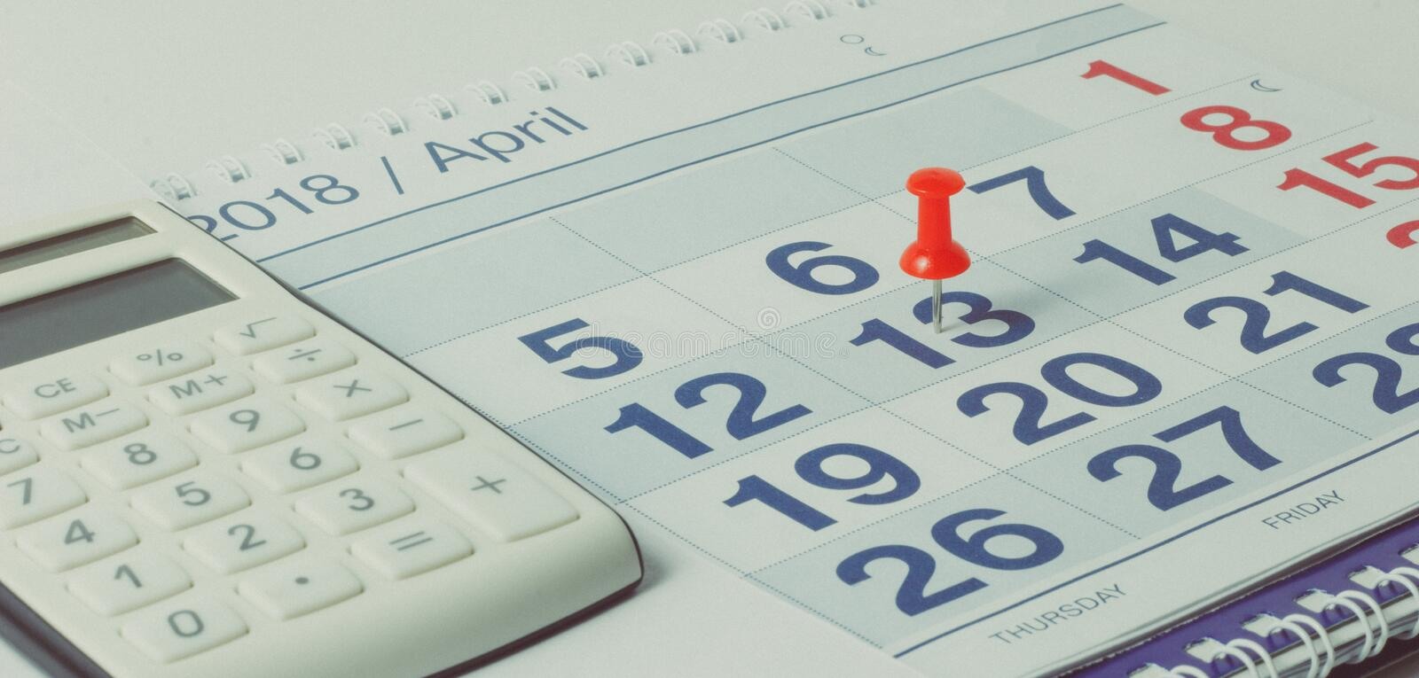 Calculator and pen on calendar background stock photography