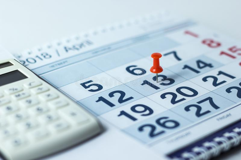 Calculator and pen on calendar background royalty free stock photo
