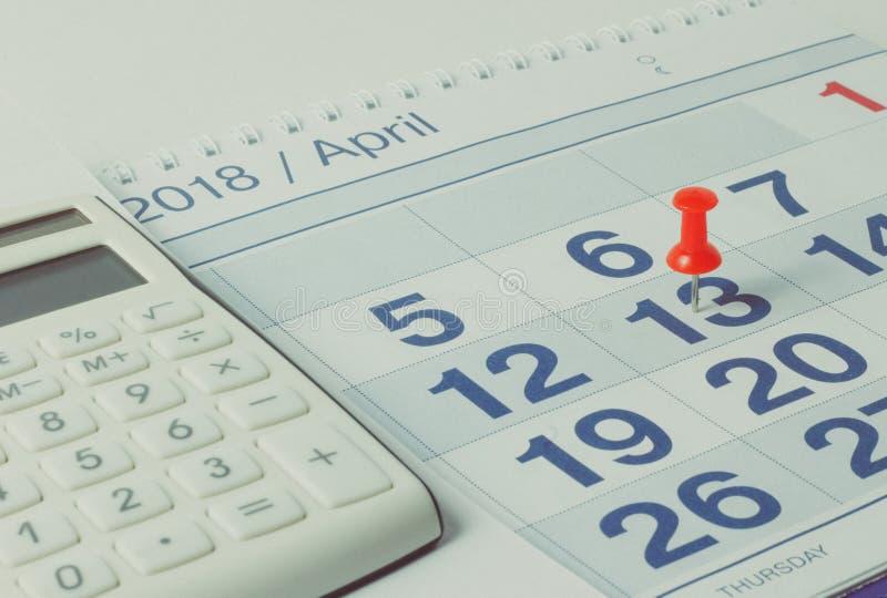 Calculator and pen on calendar background stock photos