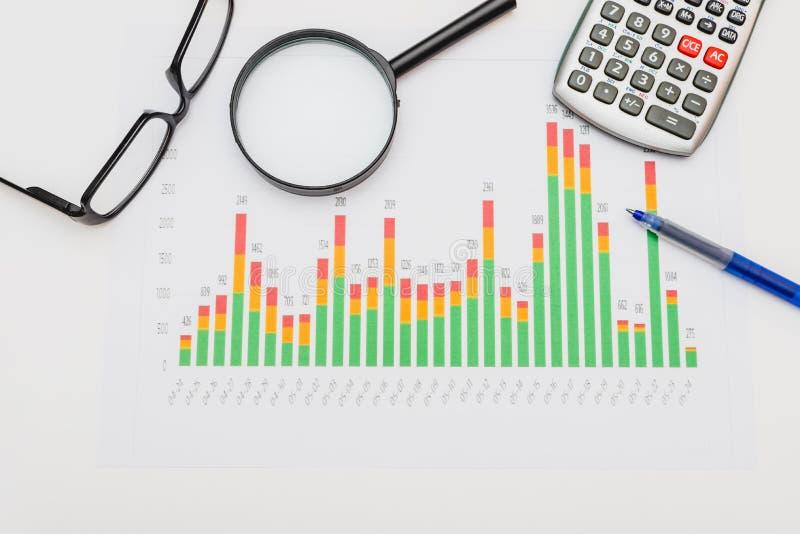 Calculator, pen en glazen met financi?le grafieken stock foto's
