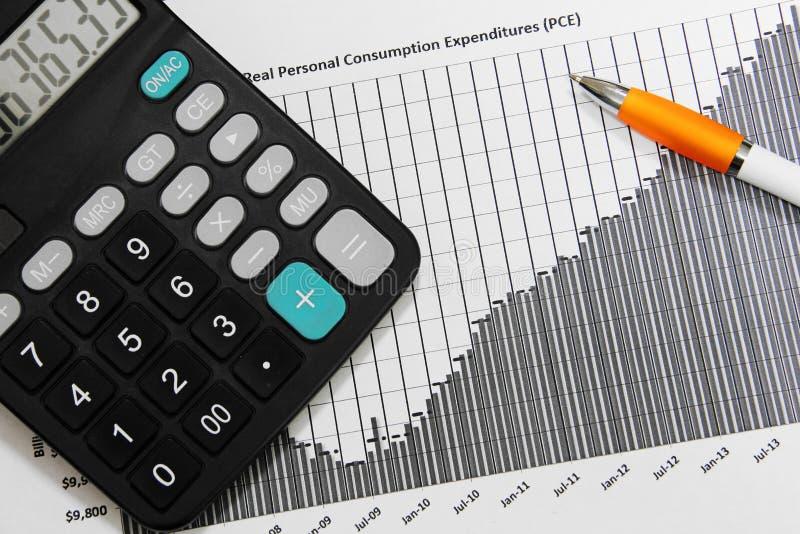 Calculator and pen with financial diagram. Black calculator and pen on top of financial diagram chart stock photos
