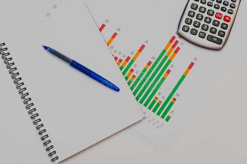 Calculator, pen and glasses with financial graphs stock photo