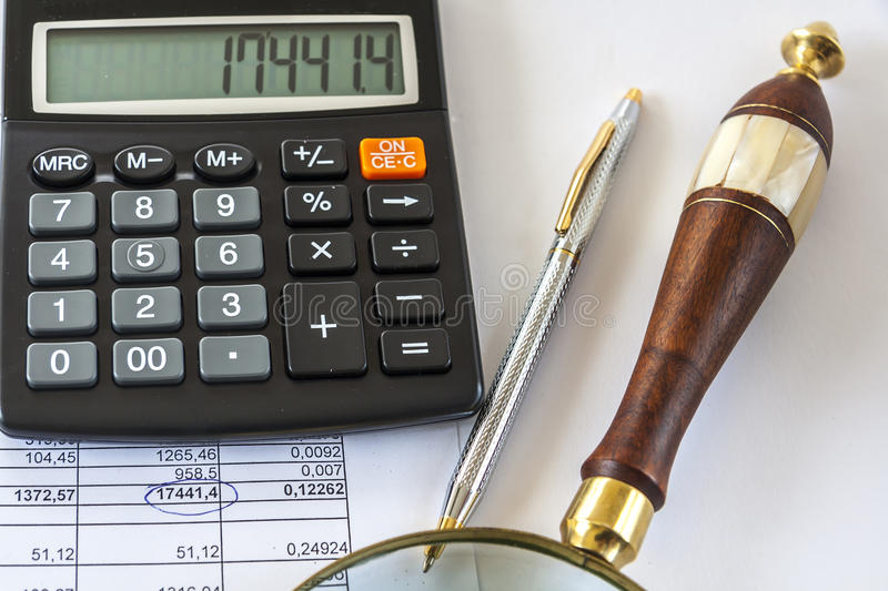 A Calculator,Pen And Magnifying Glass Sit On a Page With Numbers. Macro Image Of A Calculator,Pen And Magnifying Glass Sit On a Page With Numbers stock images