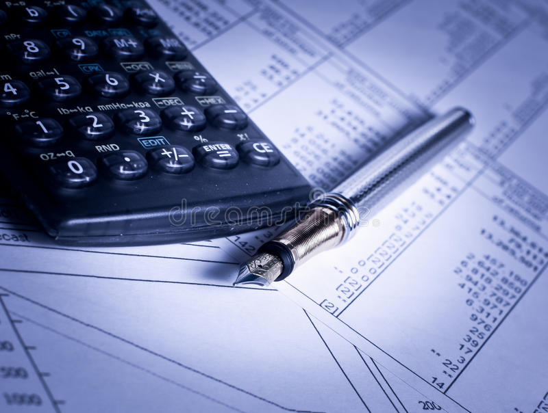 Calculator and pen on papers. Financial charts and tables lying on the table with calculator and pen stock image