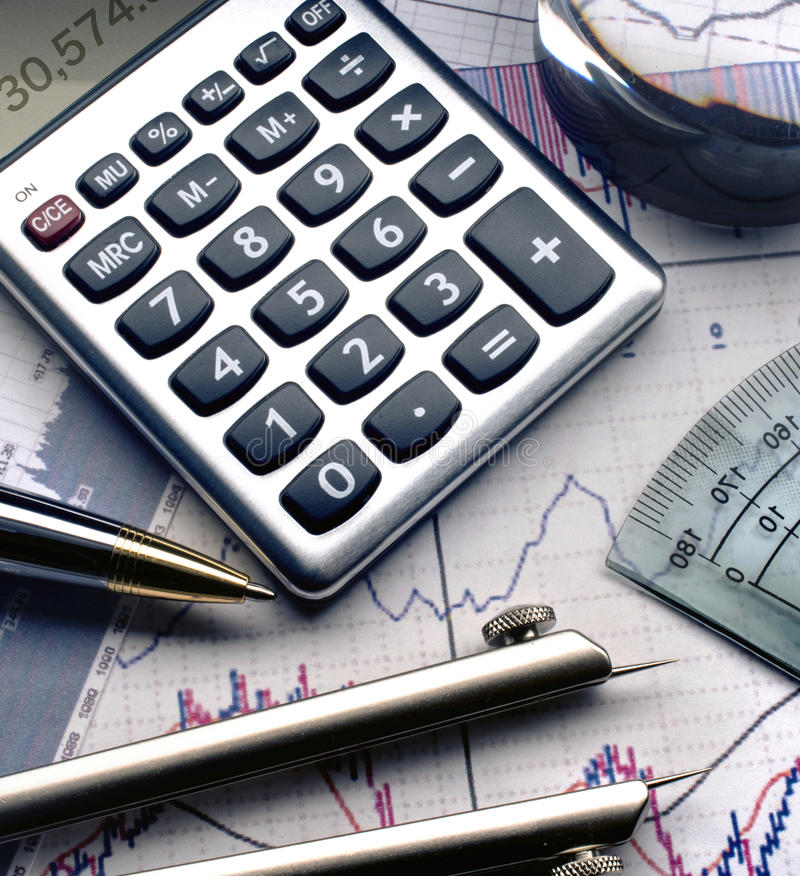 Calculator pen on stock charts and graphs