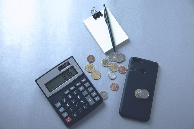 Calculator with phone and coins royalty free stock photography