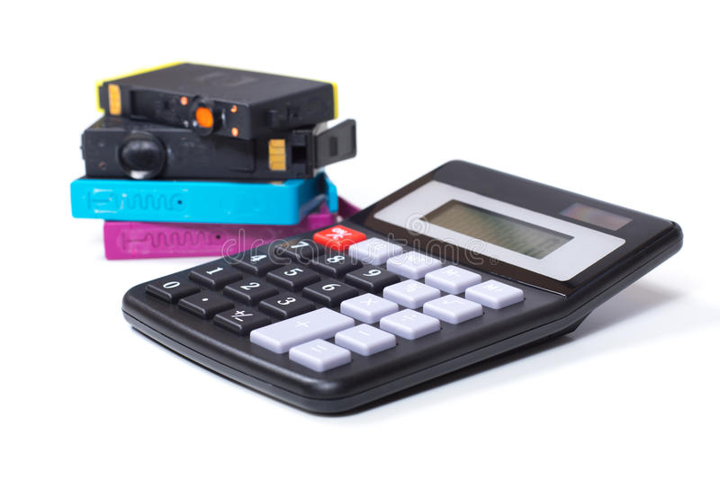 Calculator and printer ink cartridges. Color printer ink cartridges with simple calculator, close-up detail view from the side, symbolising consumables expenses royalty free stock images