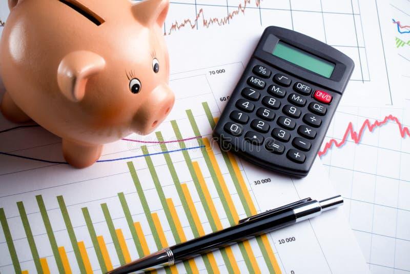 Calculator, spaarvarken en pen op bedrijfsgrafiek royalty-vrije stock afbeeldingen