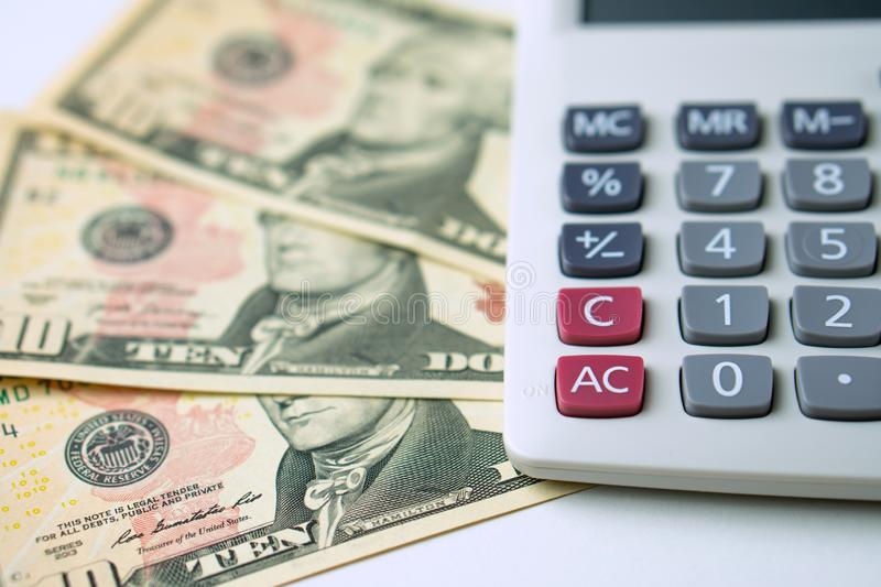 Calculator on ten dollars banknotes on a white background. Concept of Calculation of income and expenses stock image