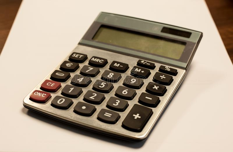 Calculator on a white piece of paper. A calculator sits on top of a white sheet of paper royalty free stock photography