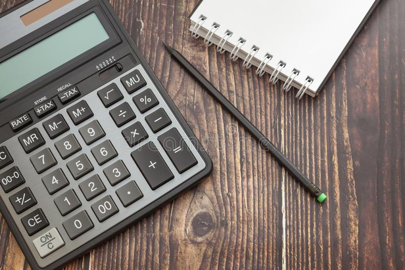 Calculator on wooden background with notepad and pencil, concept of business and saving finances stock photos