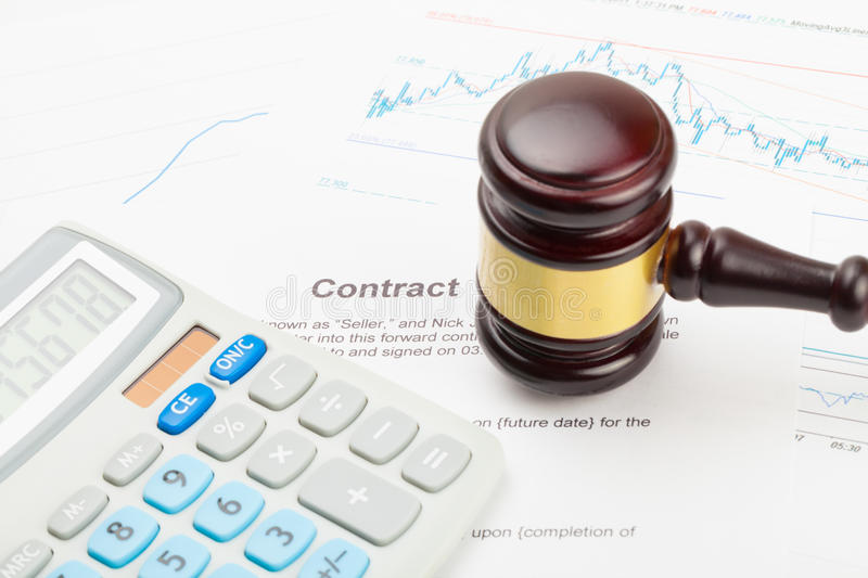 Calculator and wooden judge`s gavel over financial document - close up studio shot royalty free stock photography