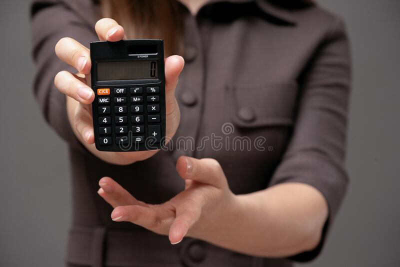 Calculator in business lady hands. Calculator with zero on the display in business lady hands close up royalty free stock photo