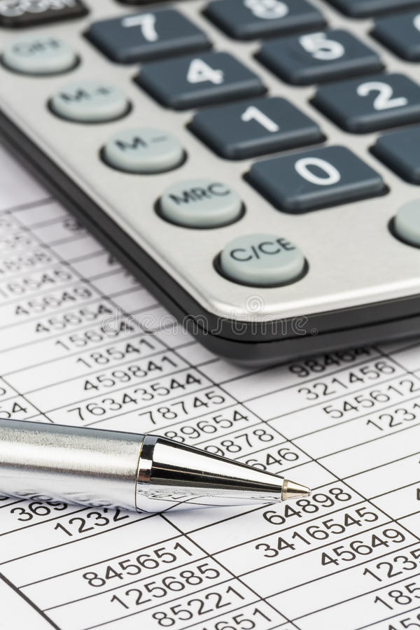 Calculators and statistk. A calculator is on a balance sheet numbers are statistics. photo icon for sales, profit and cost stock images