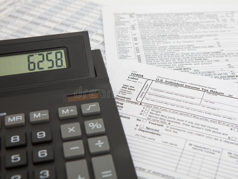 Calculatrice avec la déclaration d'impôt images stock