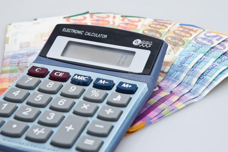 Calculatrice, billets israéliens de shekel et monnaie d'isolement sur le blanc image libre de droits