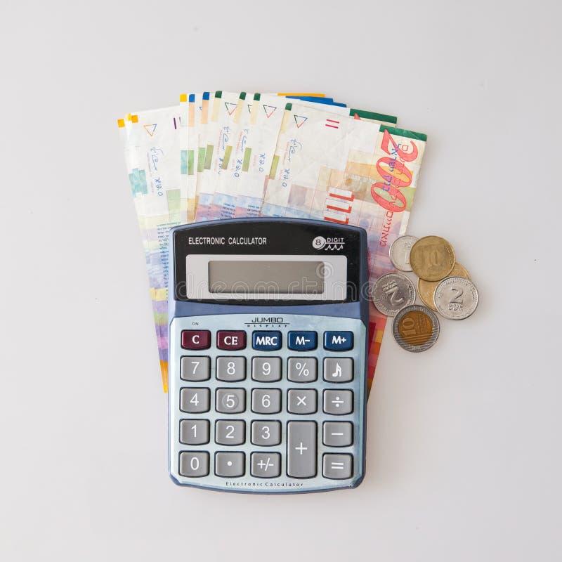 Calculatrice, billets israéliens de shekel et monnaie d'isolement sur le blanc photo libre de droits