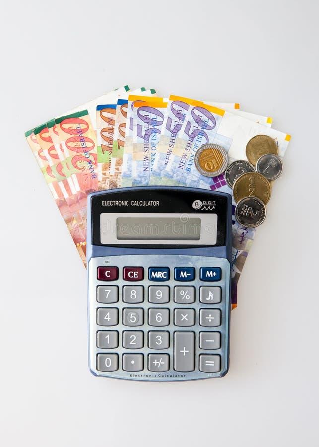 Calculatrice, billets israéliens de shekel et monnaie d'isolement sur le blanc photos libres de droits