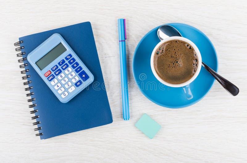 Calculatrice, bloc-notes, stylo, gomme, café dans la tasse bleue et cuillère photo stock