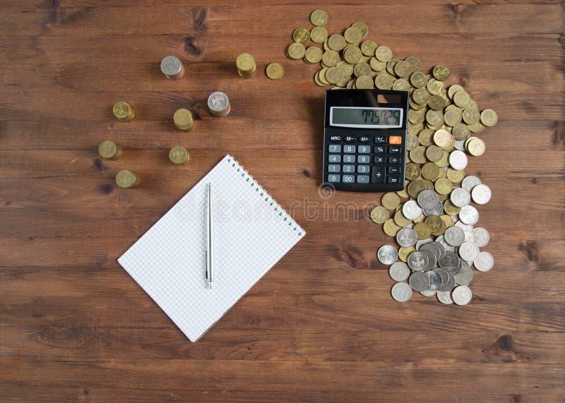 Calculatrice, carnet et pile des pièces de monnaie photos libres de droits