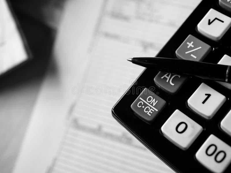 Calculatrice de bureau et un stylo au-dessus des documents étroits vers le haut du tir en noir et blanc images libres de droits