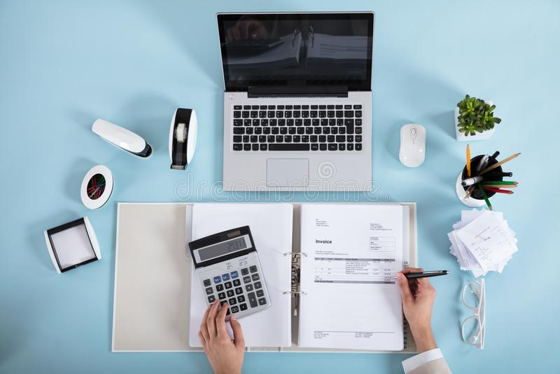 Calculatrice de Calculating Invoice Using de femme d'affaires photographie stock libre de droits