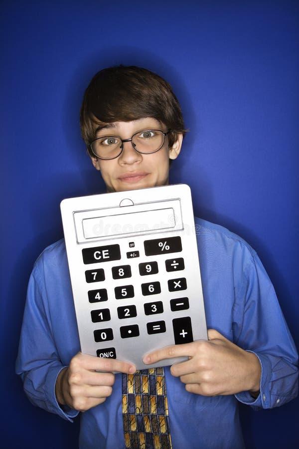 Calculatrice de l'adolescence de fixation de garçon. images stock