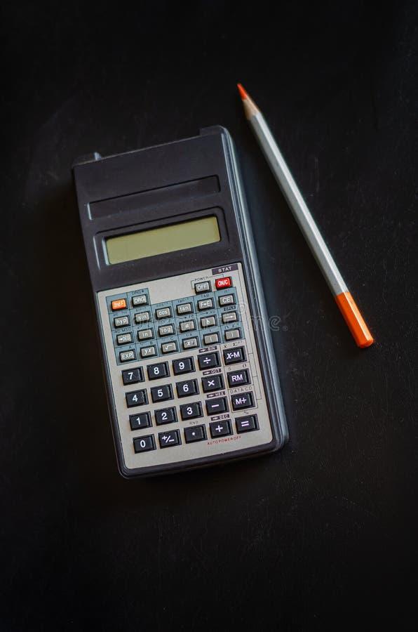 Calculatrice et crayon de cru Découvertes dans le grenier d'une vieille maison Choses antiques Fond fonc? Disposition verticale images stock