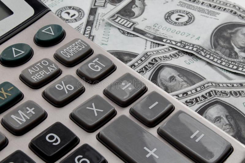 Calculatrice et dollars sur le bureau photo stock
