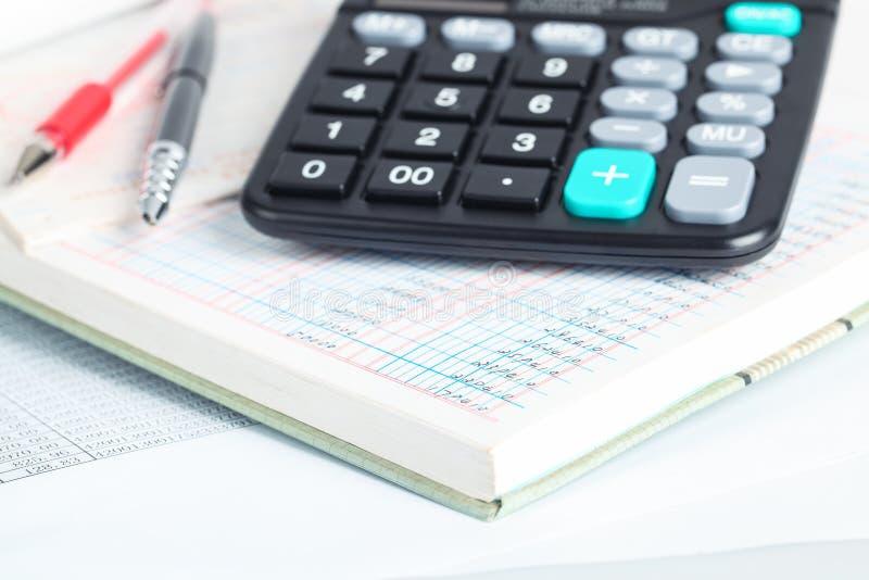 Calculatrice et livres financiers photos stock