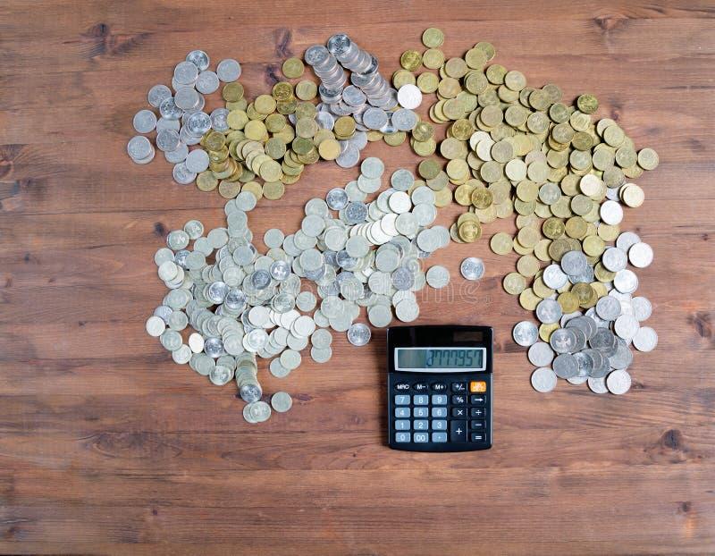Calculatrice et pile des pièces de monnaie image stock