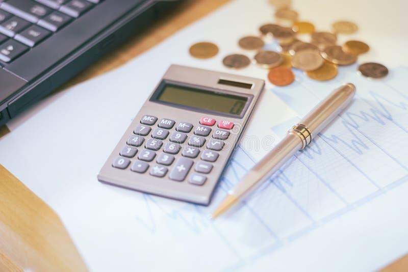 Calculatrice et stylo sur un papier avec le graphique DOF peu profond photos stock