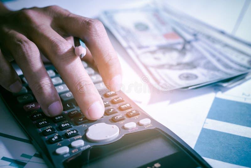 Calculatrice fonctionnante de compte, b?n?fice ou ?conomie de graphique sur des tables dans le bureau ? la maison photographie stock