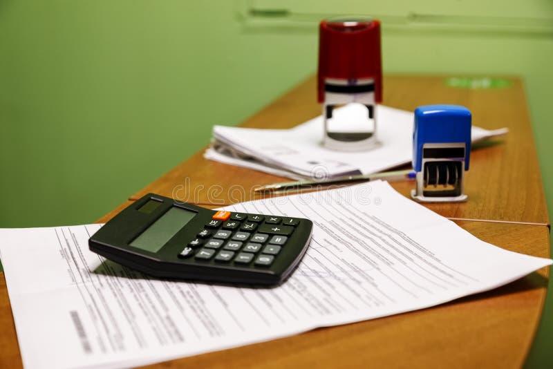 Calculatrice noire avec des papiers dans le bureau photos stock
