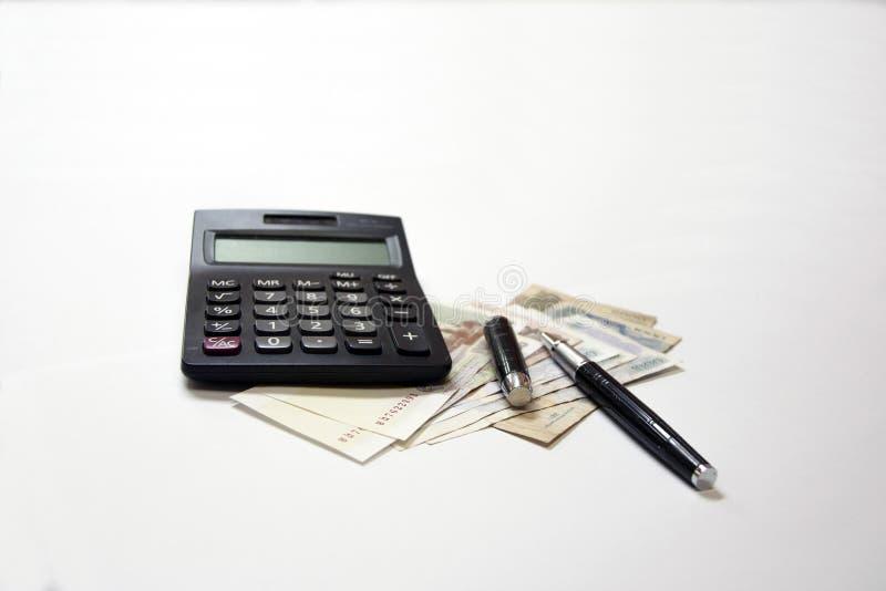 Calculatrice noire et stylo noir en métal sur le billet de banque cambodgien sur le fond blanc photo libre de droits
