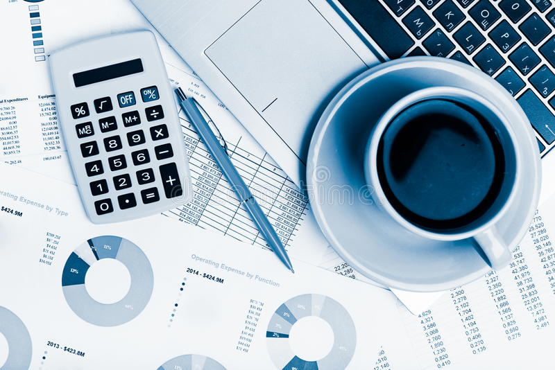 Calculatrice, ordinateur portable et tasse de café sur les documents financiers o image libre de droits