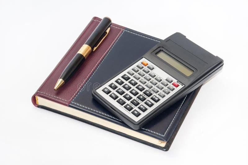 Calculatrice scientifique et stylo d'or sur le carnet d'affaires photo stock