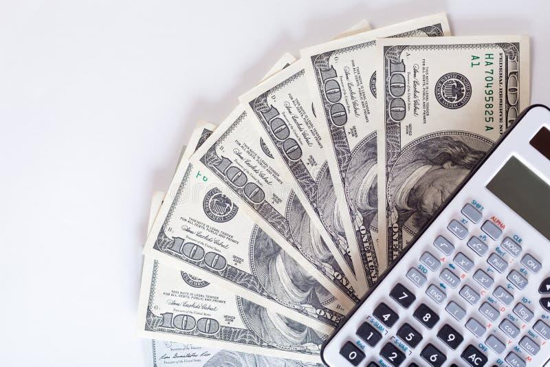 Calculatrice se trouvant sur des factures de dollar US sur un fond blanc, argent images libres de droits