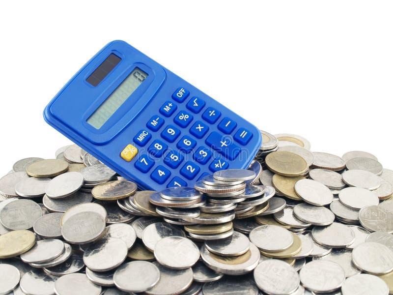 Calculatrice sur une pile des pièces de monnaie sur le fond blanc image stock