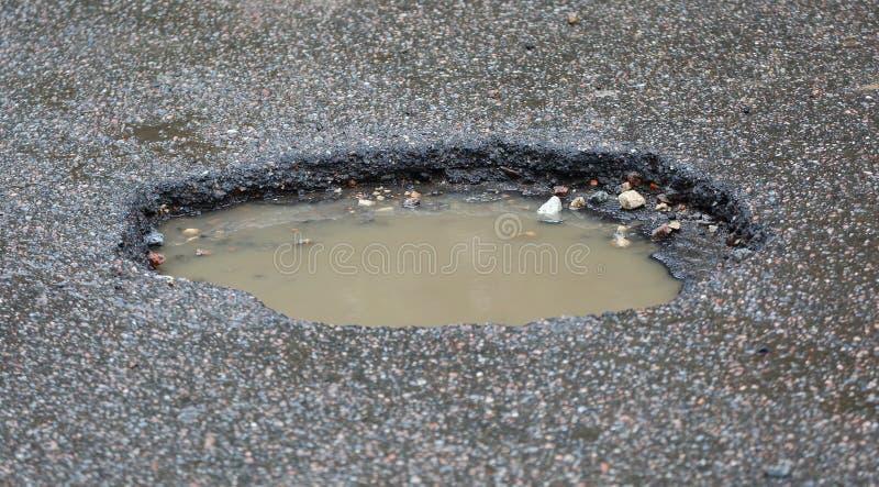 caldeirão Água-enchido na superfície da estrada asfaltada fotografia de stock royalty free