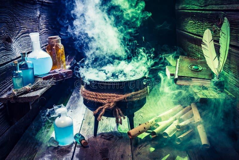Caldeirão mágico com rolos, livros e poções para Dia das Bruxas fotos de stock royalty free