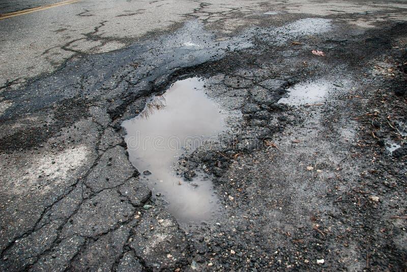 Caldeirão na estrada asfaltada fotografia de stock royalty free