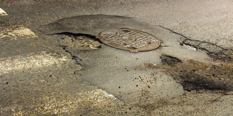 Caldeirão Waterfilled na estrada rodoviária asfaltada foto de stock royalty free
