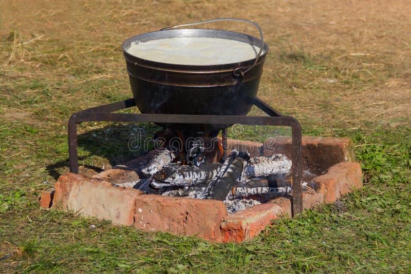Caldeira com leite de ebulição para cozinhar o queijo de Adyghe no fogo fotos de stock