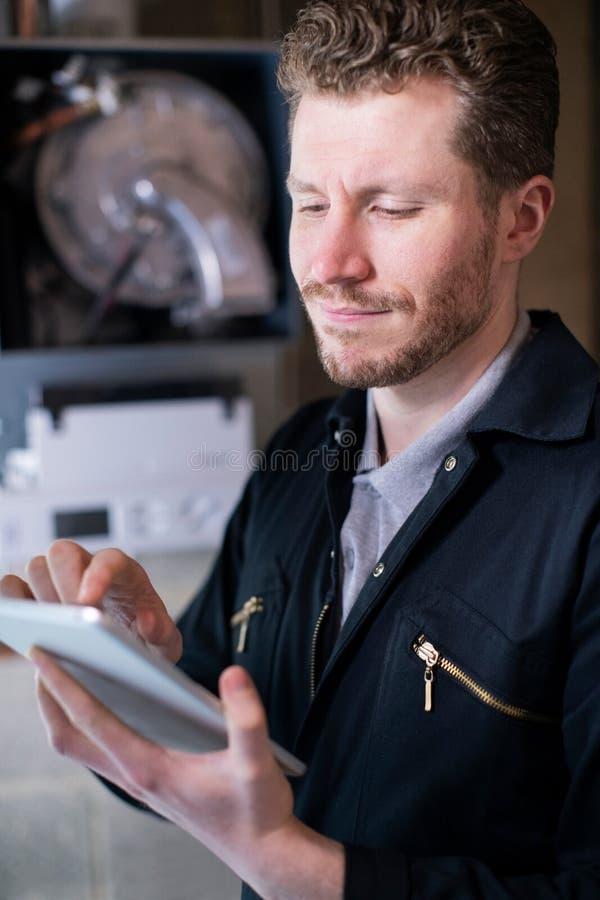 Caldeira de aquecimento masculina de Servicing Central Heating do coordenador usando a tabuleta de Digitas imagens de stock