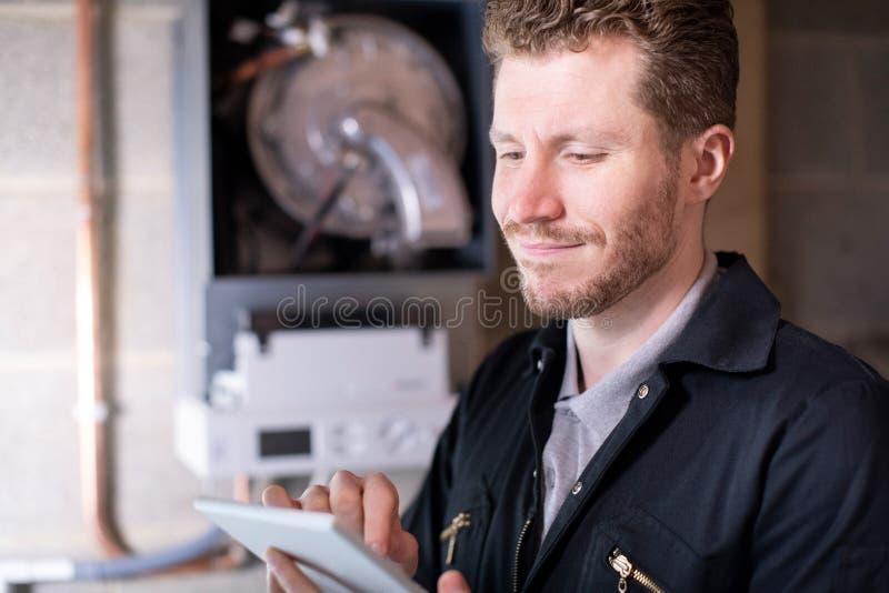Caldeira de aquecimento masculina de Servicing Central Heating do coordenador usando a tabuleta de Digitas fotos de stock royalty free