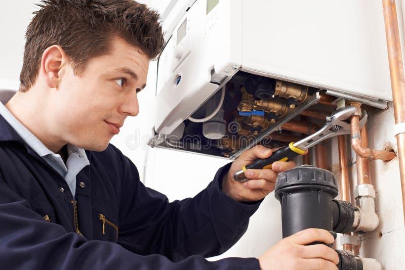 Caldeira masculina do aquecimento de Working On Central do encanador imagens de stock