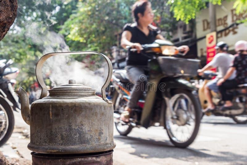 Caldera con agua del boilng para el té en la calle de Hanoi, Vietnam foto de archivo